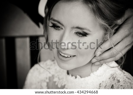 Groom's fingers touch bride's cheek while she smiles - stock photo