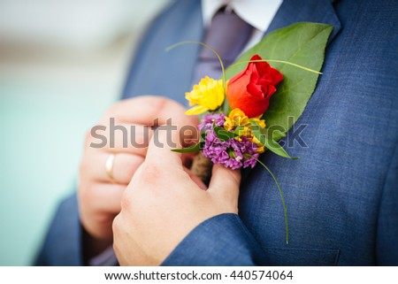 groom's hand arranging boutonniere flower on suit