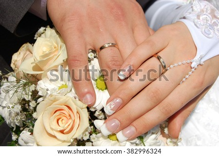 Groom 's hand on bride's hand with wedding rings and bouquet - stock photo