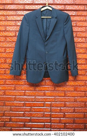 groom's suit hanging on brick wall - stock photo