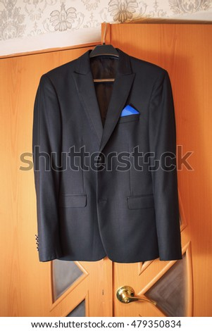 groom's suit hanging on wardrobe