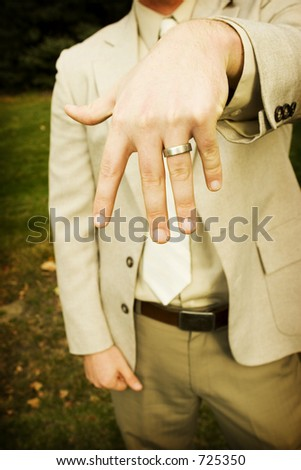 Groom showing off wedding ring - stock photo
