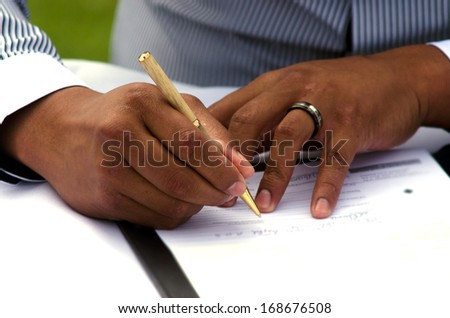 Groom signing marriage license or wedding contract. close-up - stock photo