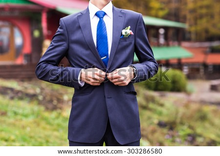groom standing in the park and looking away - stock photo