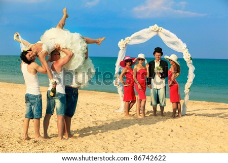 Groom standing with bridesmaids under archway on beach and waiting for his drunk bride