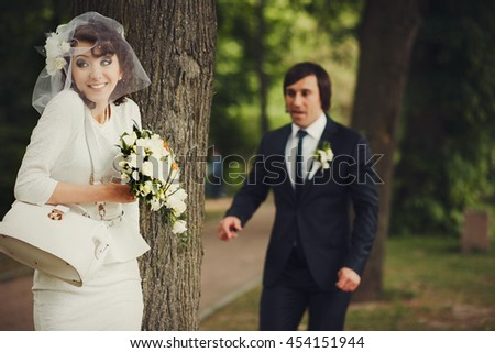 Groom steals up to the tree behind which hides a bride