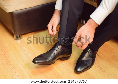 groom straining laces on wedding shoes