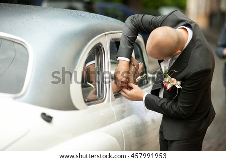 Groom takes off bride's shoes while she sits in the car