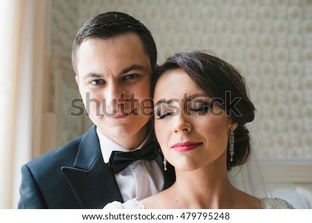 groom tenderly embraced his young wife