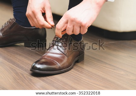groom tying cords on brown shoes