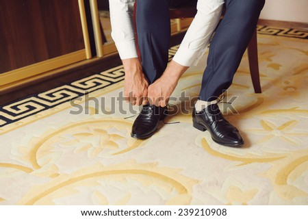groom tying laces on elegant black shoe - stock photo