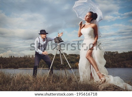 Groom using vintage photo camera outdoors  on the rock  - stock photo