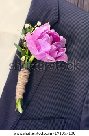 Groom wearing a purple tulip buttonhole. Close up. Toned photo