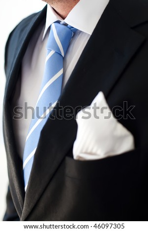 Groom wearing dark suit and a blue tie. - stock photo