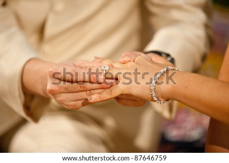 Groom wearing ring to the bride. - stock photo