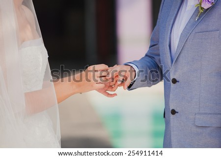Groom wearing the Diamond ring to bride hand in wedding ceremony. Wedding rings exchange - stock photo