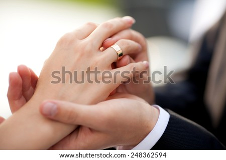 groom wears the ring on bride's finger - stock photo