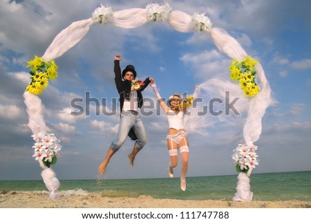 Groom with bride wearing lei, jumping under archway on beach - stock photo