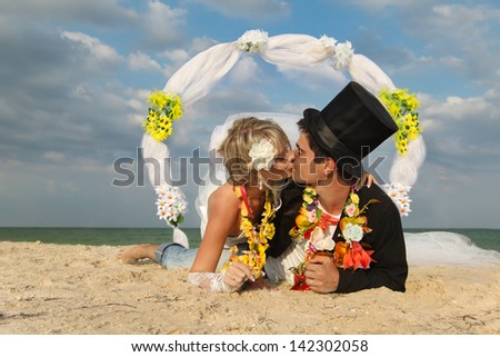 Groom with bride wearing lei lying on beach - stock photo