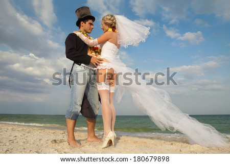 Groom with bride wearing lei on beach - stock photo