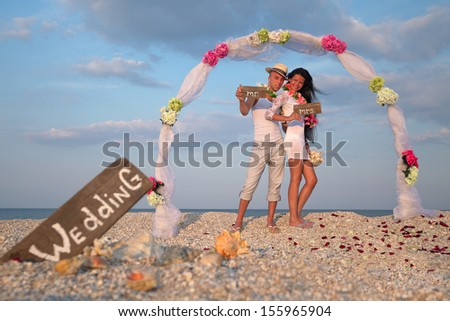 Groom with bride wearing lei, standing under archway on beach - stock photo