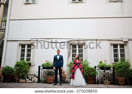 Groom with bride with warm blankets near house with windows and decorated buttles