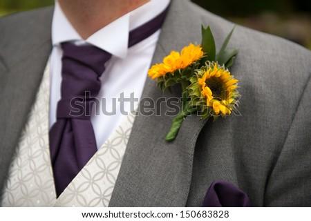 groom with sunflower wedding buttonhole - stock photo