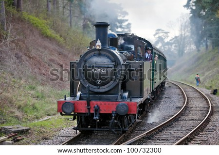 GROOMBRIDGE, ENGLAND - APRIL 15: Jinty tank engine 47493 approaches Groombridge station with a train of enthusiasts during the Spa Valley Railway spring steam gala on April 15, 2012 at Groombridge - stock photo