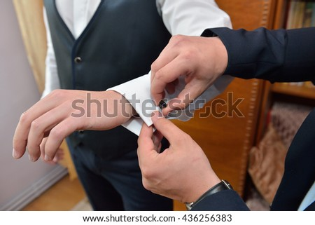 Grooms man helps the groom to put on black cufflinks on white sleeve of the shirt. Details of the morning of the wedding day