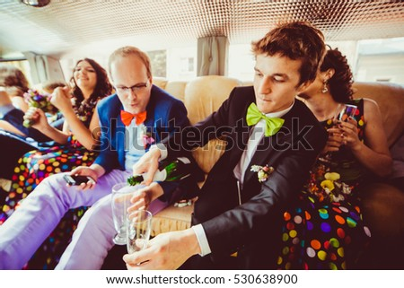 Groomsman in green bow tie pours champagne while sitting in the limousine