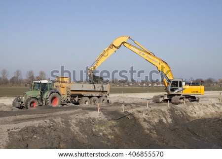 GROOTEBROEK, THE NETHERLANDS - MARCH 17, 2016: Cranes at work excavating and creating the ground in a tipper of a tractor on march 17, 2016  in Grootebroek , the netherlands. - stock photo