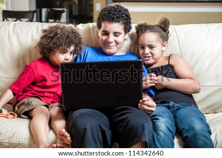 grop of three kids at home looking at laptop computer - stock photo