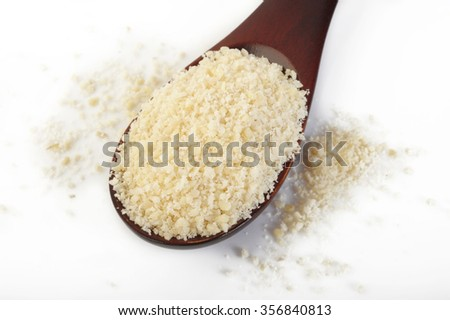 Ground almond in a wooden spoon