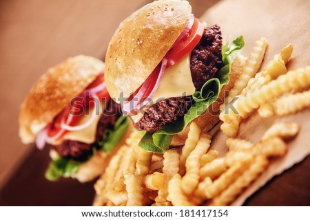 Ground beef Cheese Burger with Lettuce,Tomato and Red Onion with French Fries - stock photo