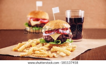 Ground beef Cheese Burger with Lettuce,Tomato and Red Onion with French Fries and glass of Cola - stock photo