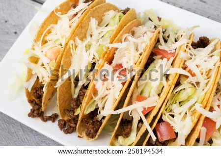 Ground beef tacos with cheese lettuce and tomatoes against wooden background - stock photo