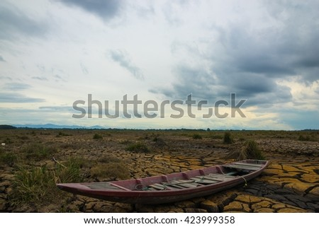 Ground broken by the drought ship aground in hard dramatic tone before rainy. Picture tone is low key style. - stock photo