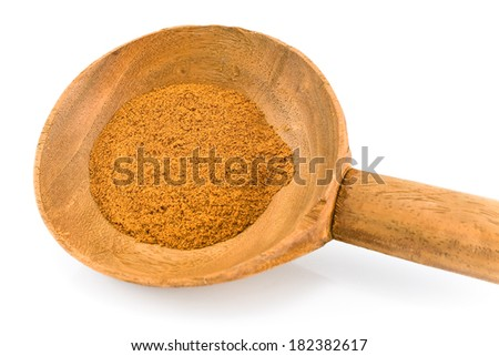 Ground chili with wooden spoon isolated on white
