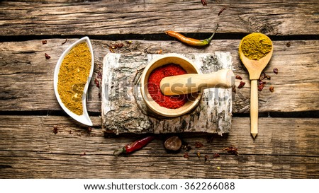 Ground chilli in a mortar with birch stand. On wooden background. Top view - stock photo