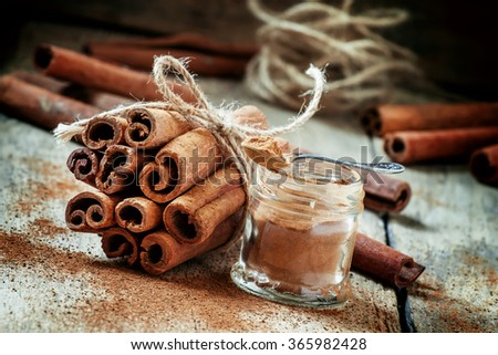 Ground cinnamon, cinnamon sticks, tied with jute rope on old wooden background in rustic style, selective focus - stock photo