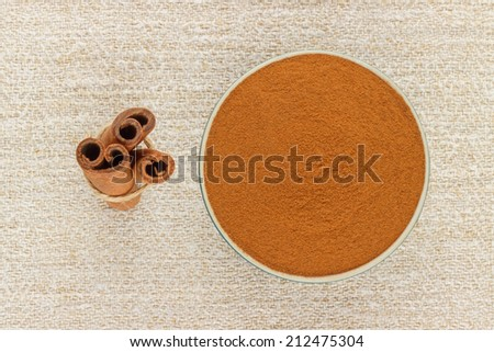 Ground cinnamon powder in porcelain bowl and cinnamon sticks on rustic table cloth, seen from above