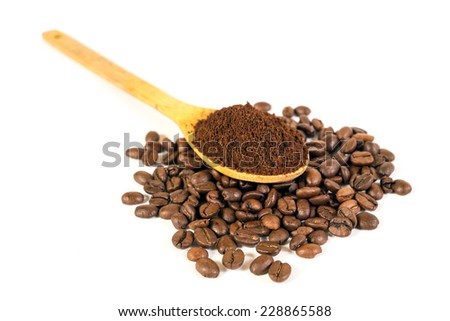 Ground coffee arabica on wooden spoon. Scattered coffee beans. White background - stock photo