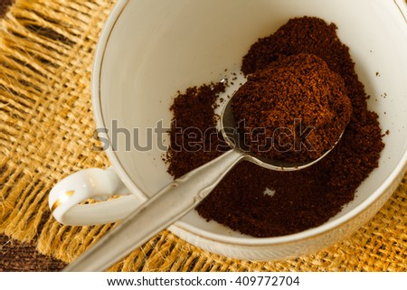 Ground coffee in a spoon on coffee cup, close up