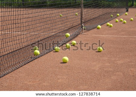 Ground court with net and many yellow tennis balls - stock photo
