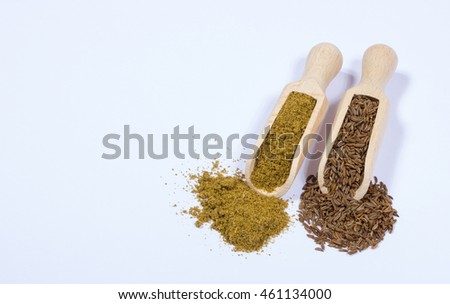 Ground cumin in a spoon and whole cumin isolated on white background.
