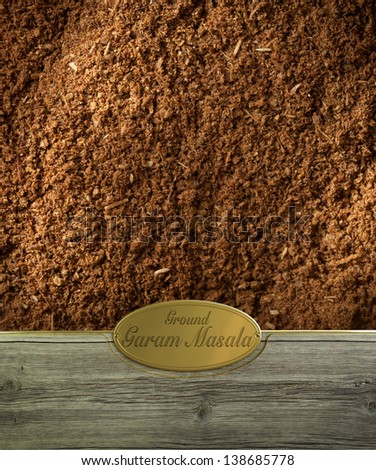 Ground Garam masala spices frame in wood with a golden label - stock photo