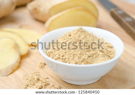 ground ginger in white bowl on a wooden board - stock photo