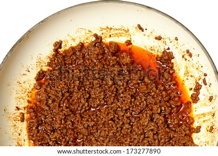Ground Lean Beef with mexican seasoning and water cooking  in Ceramic Pan over white. - stock photo