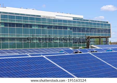 Ground level solar panel array in front of office building - stock photo