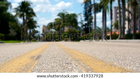 Ground level view of road between yellow lines, shallow depth of field.